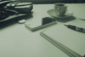 telefon-otwarty-notatnik-i-kawa-na-bialym-stole