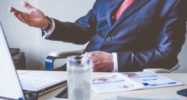 biznesmen-za-biurkiem-laptop-biuro-garnitur